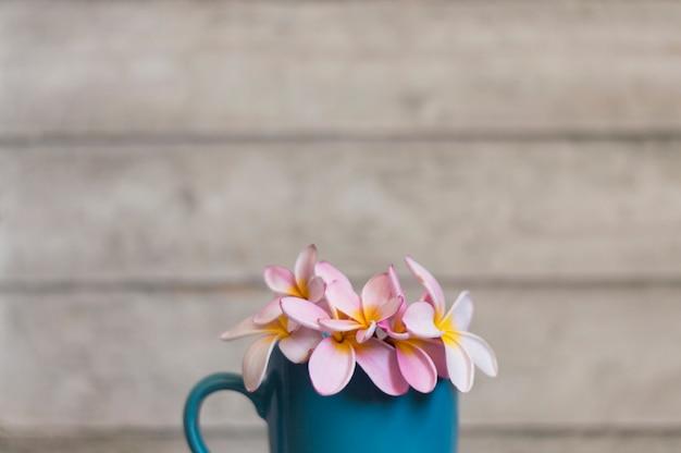 Decoratieve mok met bloemen en wazig backgroun Gratis Foto