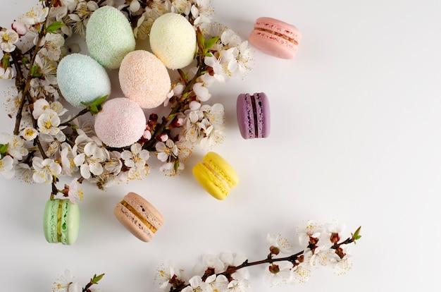 Decoratieve paaseieren en zoete macarons of bitterkoekjes ingericht Premium Foto