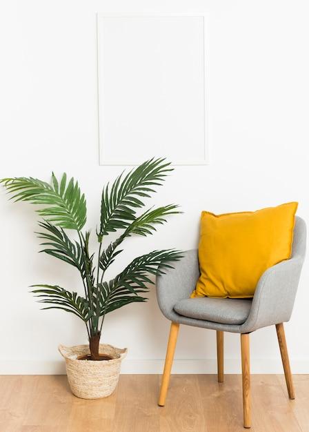 Decoratieve plant met leeg frame en stoel Gratis Foto