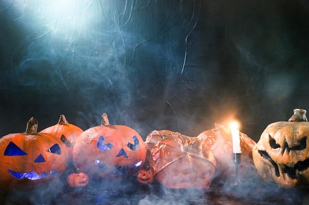 Decoratieve pompoenen in halloween-stijl en brandende kaars en rook Gratis Foto