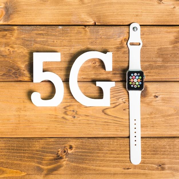 Decoratieve symbolen 5g en slimme horloge op bureau Gratis Foto
