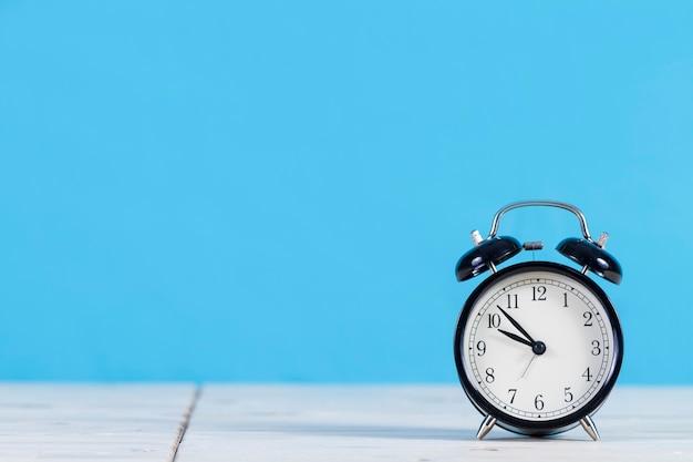 Decoratieve wekker met blauwe achtergrond Premium Foto