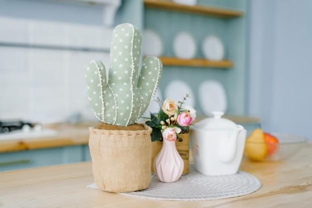 Decoratieve zachte cactus in een pot. roze vaas met bloemen en een witte ketel in het decor van de keuken in de scandinavische stijl, minimalistisch beknopt Premium Foto
