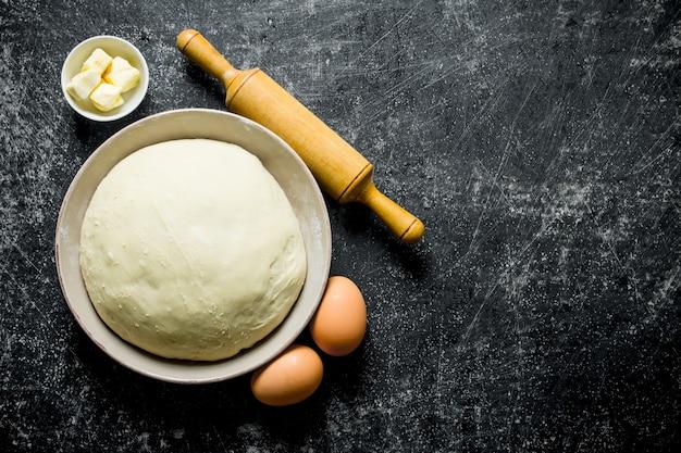 Deeg in een kom met eieren, deegroller en boter. op donkere rustieke achtergrond Premium Foto