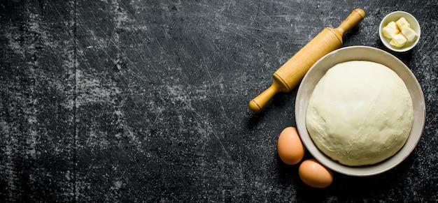 Deeg in kom met eieren, deegroller en boter op rustieke tafel Premium Foto