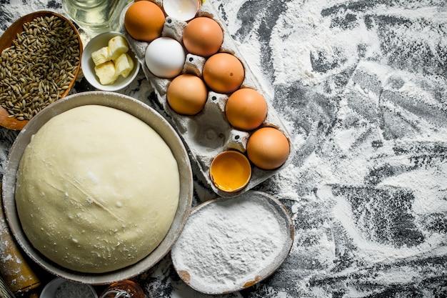 Deeg met eieren, boter en graan in kommen. op rustiek Premium Foto