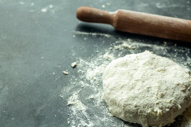 Deeg pizza achtergrond. koken pizzadeeg of brood op de keukentafel. voedsel achtergrond Premium Foto