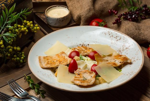 Deegwaren met gegrilde kippenplakken en tomaten in witte kom. beeld Gratis Foto
