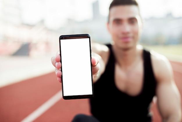 Defocused jonge mannelijke atleet die het mobiele telefoonscherm naar camera tonen Gratis Foto