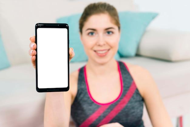 Defocussed jonge vrouwenzitting dichtbij de bank die smartphone met het lege witte scherm toont Gratis Foto