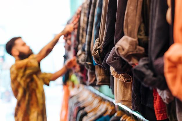 Defocussed man die overhemd van het spoor in de winkel kiest Gratis Foto