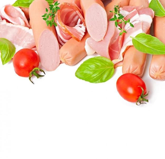 Delicaat vlees (worst en ham) versierd met basilicum en tomaten geïsoleerd Gratis Foto