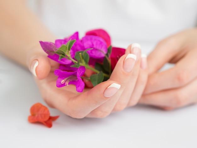 Delicate gemanicuurde handen met bloemen Gratis Foto