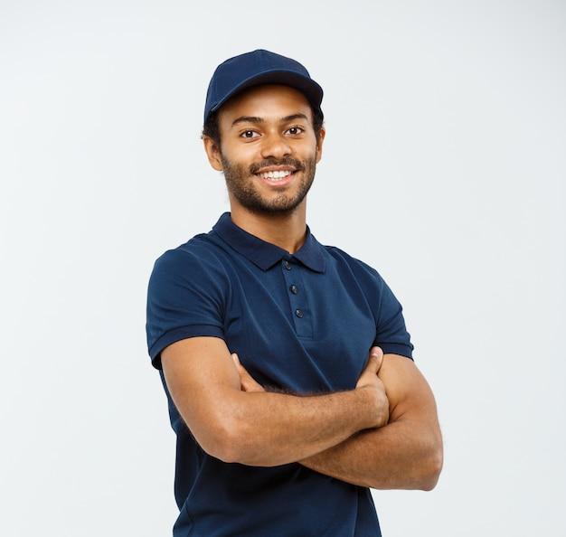 Delivery concept - knappe afro-amerikaanse leverancier man gekruiste armen over geïsoleerd op grijze studio achtergrond. ruimte kopiëren. Gratis Foto