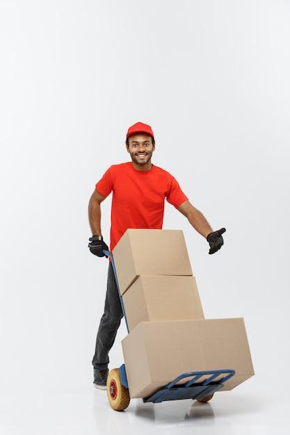 Delivery concept - portret van knappe afro-amerikaanse leverancier of koerier duwen handwagen met stapel dozen. geïsoleerd op grijze studio achtergrond. ruimte kopiëren. Gratis Foto