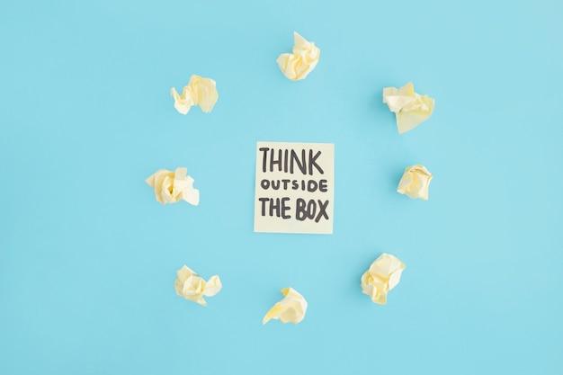 Denk buiten de tekst van de doos op zelfklevende notitie omringd met geel verfrommeld papier over de blauwe achtergrond Gratis Foto