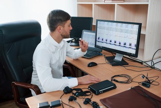 Denken en conclusies trekken. polygraaf-examinator werkt op kantoor met de apparatuur van zijn leugendetector Gratis Foto