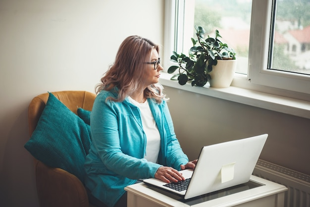 Denken kaukasische senior vrouw met blond haar en bril werken op de computer bij het raam tijdens de quarantaine Premium Foto