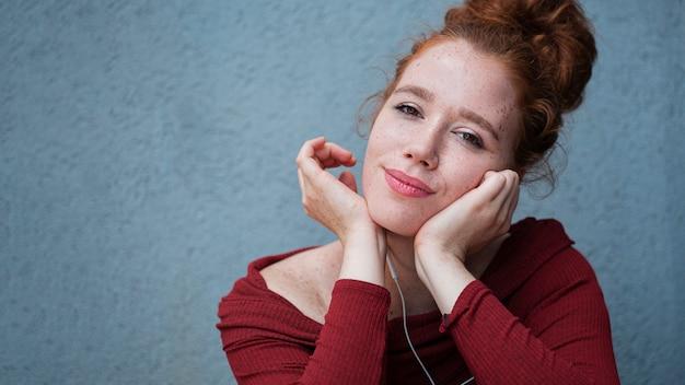 Denkende jonge dame die naar muziek luistert Gratis Foto