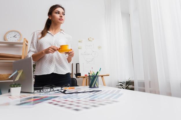 Denkende vrouw die een kop koffie houdt Gratis Foto