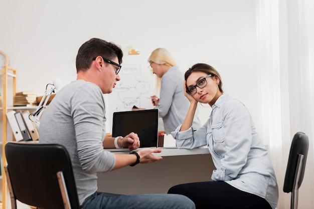 Denkende vrouw die met de mens op kantoor spreekt Gratis Foto
