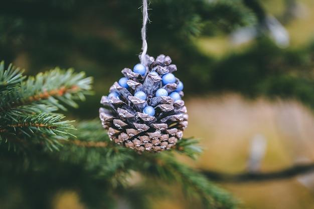 Denneappel met blauwe parels op kerstboom. Premium Foto