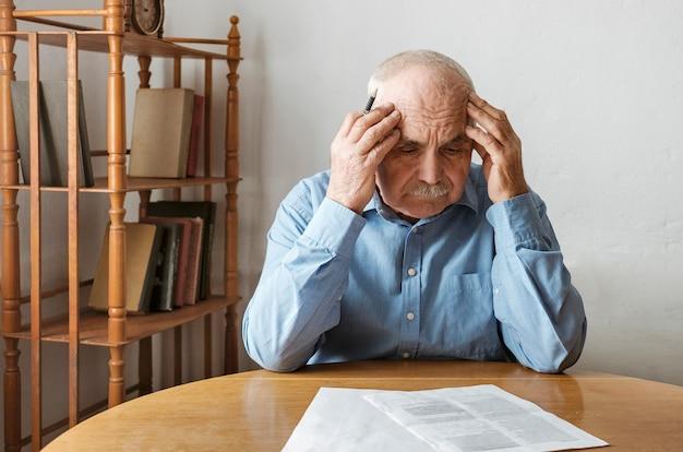 Depressief, bezorgde senior man die papierwerk doet Premium Foto