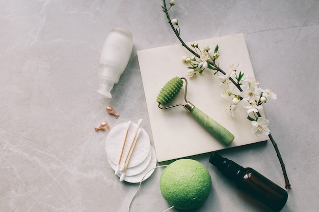 Dermaroller en serum naast een anti-aging gezichtscrème schoonheidsindustrie dermaroller voor medische micro-naaldbehandeling derma-rolmesoroller voor mesotherapie bij bloemen Premium Foto