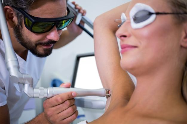 Dermatoloog die haar van de oksel van de patiënt verwijdert Gratis Foto