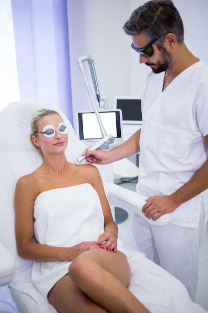 Dermatoloog die mol van de schouder van de vrouw verwijdert Gratis Foto