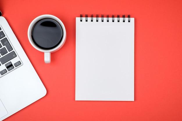 Designerbureau met lege notitieboekjepagina en laptop Premium Foto
