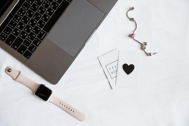 Desktop-items: laptop, smartwatch, accessoires voor vrouwen, bovenaanzicht Premium Foto
