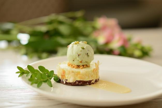 Dessert met een bal van pistacheroomijs met bloemdecor Premium Foto