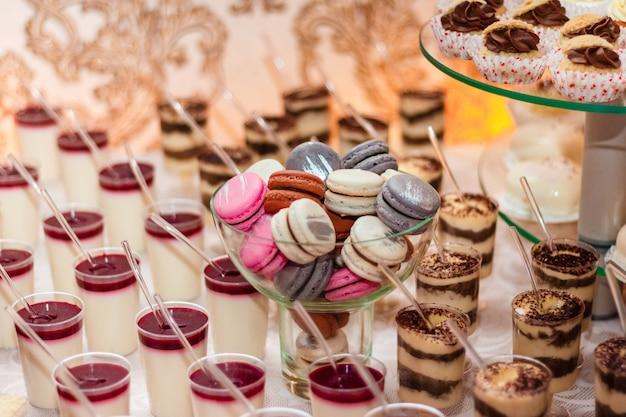 Desserts met mousse, koekjes. verschillende soorten zoet gebak, kleine kleurrijke zoete taarten, macaron en andere desserts in het zoete buffet. Premium Foto