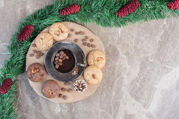 Dessertset met koekjes en boom naast groene slinger op marmer. Gratis Foto