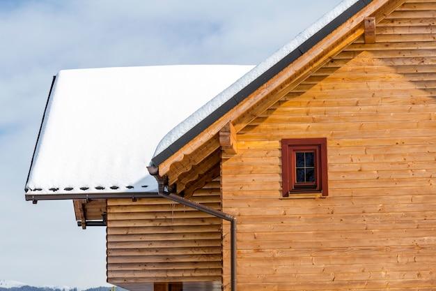 Detail bovenkant van houten ecologische traditionele cottage van timmerhout materialen met steil dak, zolderkamers bedekt met sneeuw op zonnige winterdag. oude tradities en modern professioneel bouwconcept. Premium Foto