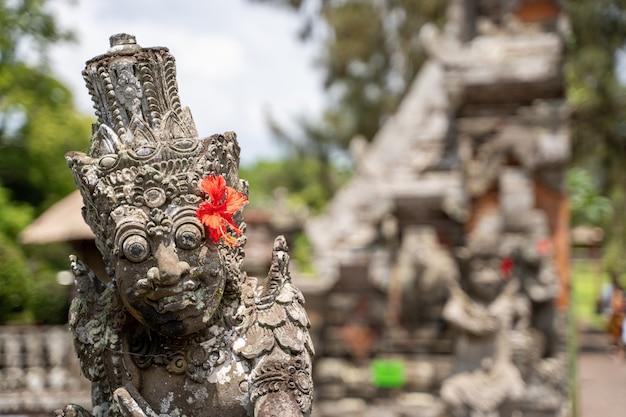 Detail van de bovenkant van een stenen beeld in een hindoe-tempel met een rode bloem Premium Foto