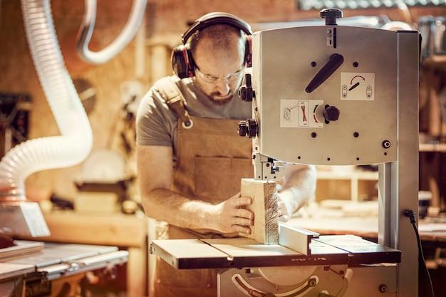 Detail van een timmerman aan het werk die een plank met een lintzaag in zijn workshop snijdt Premium Foto