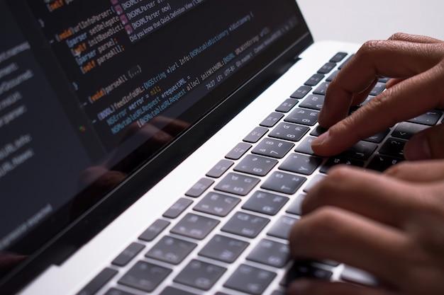 Detailopname. de hand van de ontwikkelaar maakt code op een computermonitor op een wit bureau. Premium Foto