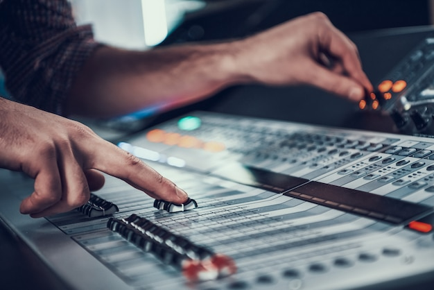 Detailopname. mannelijke handen die audiocontrolemechanisme aanpassen. Premium Foto