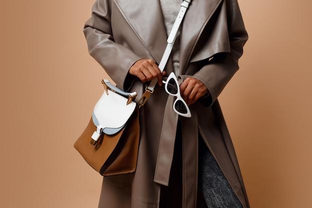 Details. zwarte die grijze leerlaag dragen, die op beige achtergrond stellen. bruine tas en witte zonnebril in handen. herfst of winter mode concept. Gratis Foto