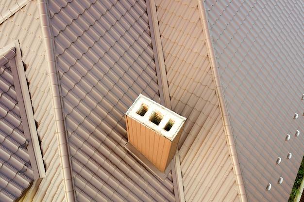 Detailweergave van het dak van het huis bedekt met bruine metalen tegelplaten. Premium Foto