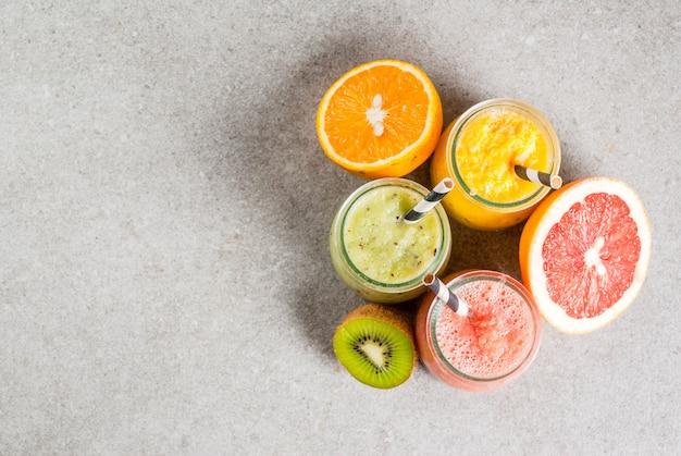 Detox biologische dieetdranken, zelfgemaakte tropische smoothies - kiwi, sinaasappel, grapefruit, in geportioneerde potten, met ingrediënten, op een grijze stenen tafel. copyspace bovenaanzicht Premium Foto