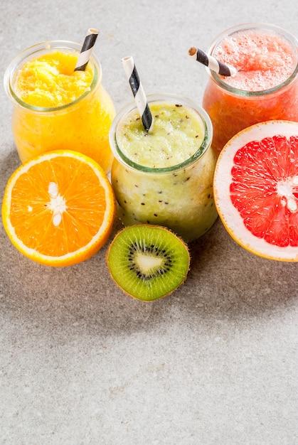 Detox biologische dieetdranken, zelfgemaakte tropische smoothies kiwi, sinaasappel, grapefruit, in geportioneerde potten, met ingrediënten, op een grijze stenen tafel. Premium Foto