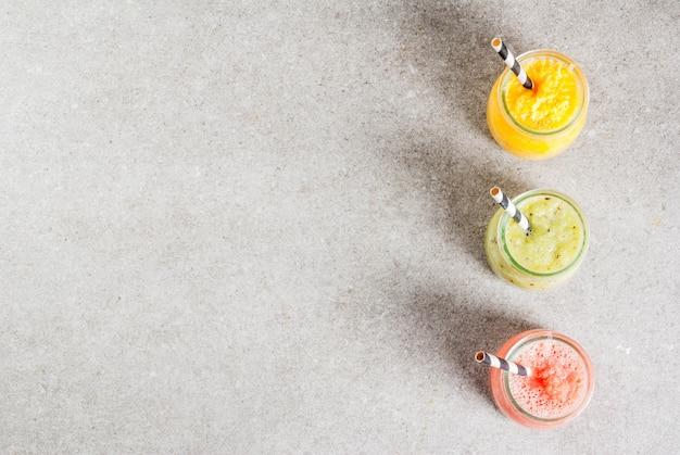 Detox biologische dieetdranken, zelfgemaakte tropische smoothies - kiwi, sinaasappel, grapefruit, in geportioneerde potten, op een grijze stenen tafel. copyspace bovenaanzicht Premium Foto