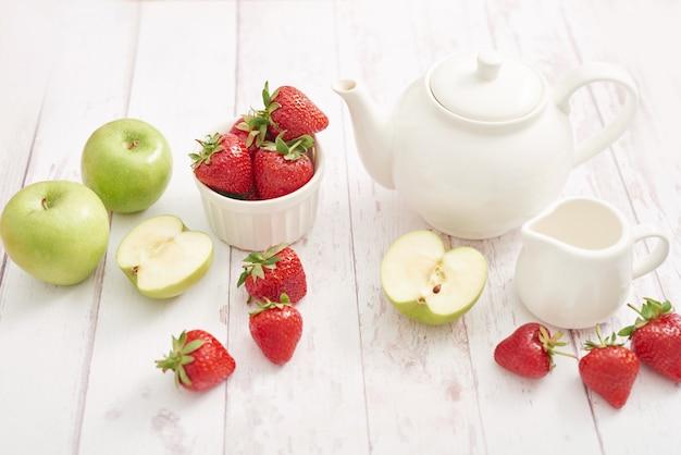 Detox concept. lekker fruit en bessen. gezond eten. veganisme, vegetarisme, rauwkostdieet. aardbeien en appels. zomer vers fruit. kopieer ruimte. vitaminen in voedsel. gezond ontbijt. thee set Premium Foto
