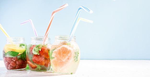 Detox smoothies van verse groenten en fruit in glazen potten met buizen Premium Foto
