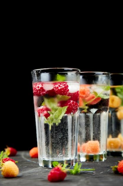 Detox toegediend gearomatiseerd water met drie kleuren framboos Premium Foto