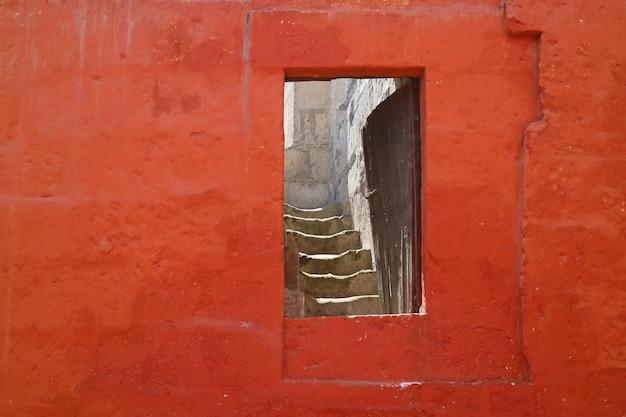 Deuropening op rode steenmuur die tot de trap binnen een oud gebouw, arequipa, peru leidt Premium Foto