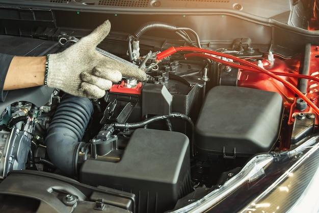 Deze carrière-inspectie aziatische man autodienst het laden batterijauto Premium Foto